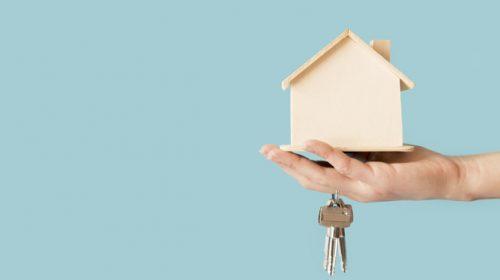 close-up-hand-holding-keys-wooden-house-model-against-blue-background_23-2148038680