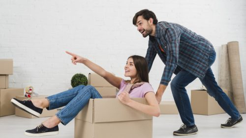 happy-couple-is-having-fun-with-cardboard-boxes-new-house_23-2148095521